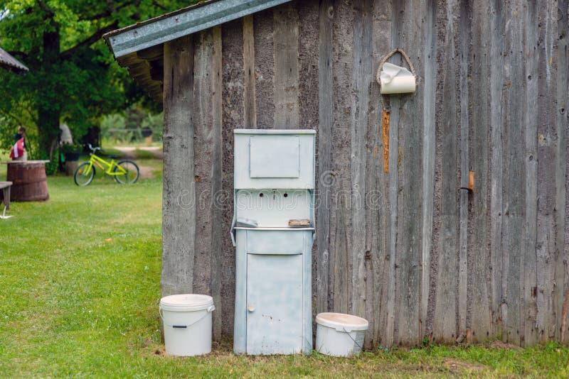 На сельском доме флигели огораживают аранжированный старомодный деревенский умывальник стоковые фотографии rf