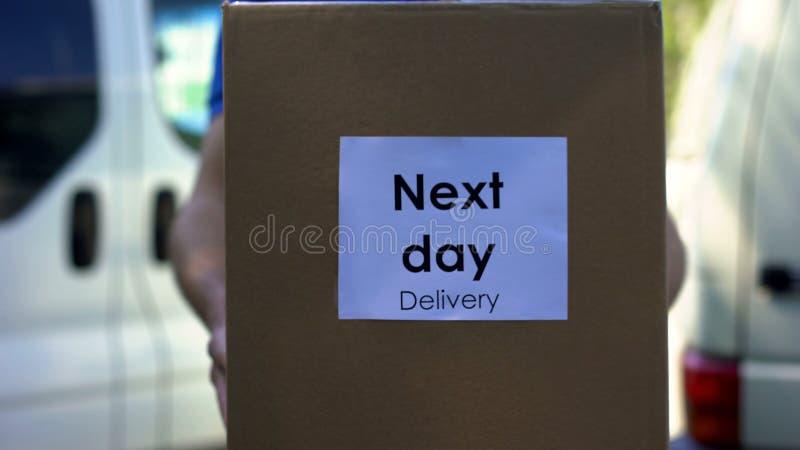 На следующий день курьер поставки в равномерном держа обслуживании картонной коробки международном стоковое фото