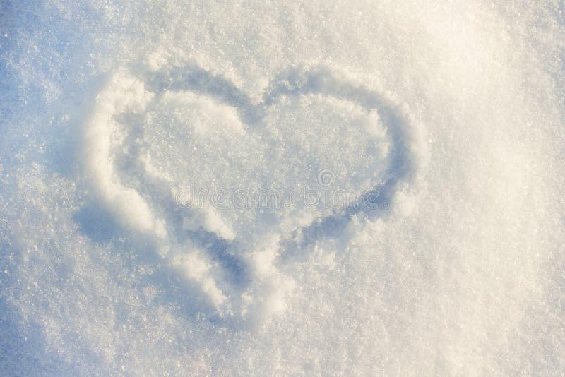 На солнц-освещенном покрашенном снеге сердцу, символ влюбленности в difficu стоковая фотография rf