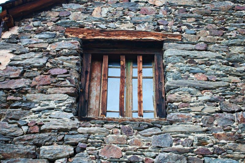 На старом окне каменного здания для обеспечения безопасности установлены вертикальные деревянные планки стоковая фотография rf