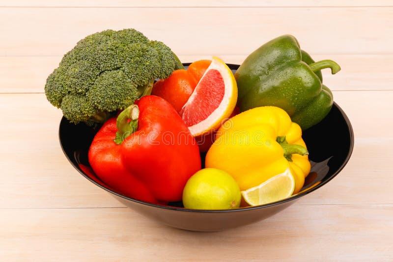 На таблице в плите овощи и цитрусовые фрукты indoors стоковые фото