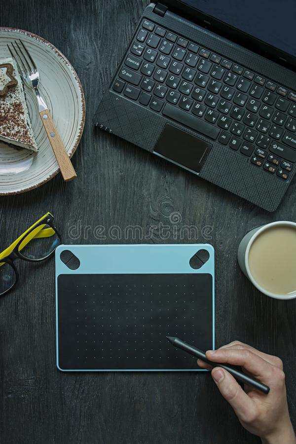 На таблице ноутбук, планшет графиков и чашка кофе Канцелярские товары Рабочая Среда r Темное деревянное стоковое изображение