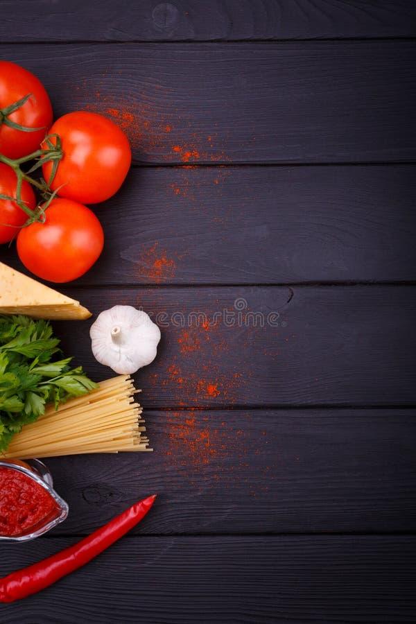 На таблице, плане спагетти, вишне, петрушке, перце и чесноке над взглядом Конец-вверх indoors стоковые изображения