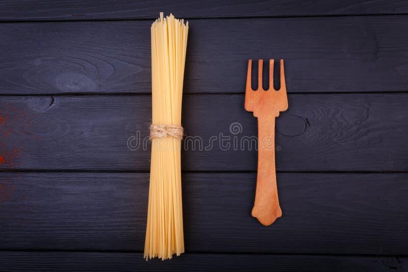 На таблице пук спагетти и деревянной вилки над взглядом indoors стоковая фотография rf