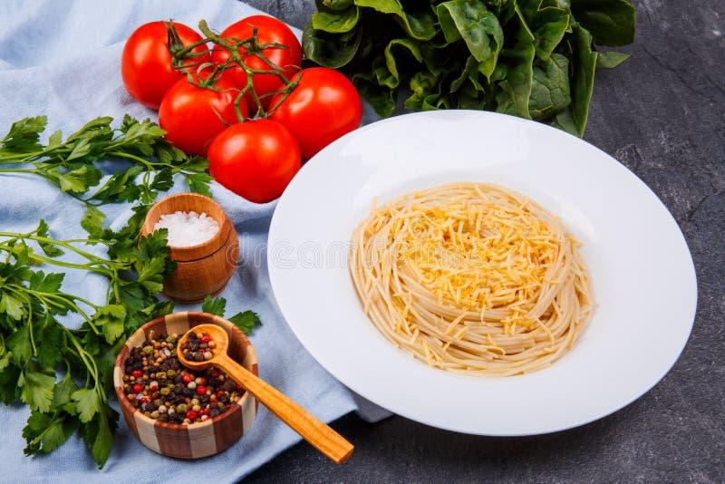 На таблице спагетти с сыром, зелеными цветами, томатами и смесью перцев стоковая фотография rf