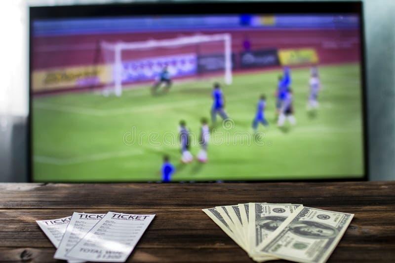 На ТВ футбол на таблице держит пари билеты и доллары денег, резвятся пари стоковые изображения rf