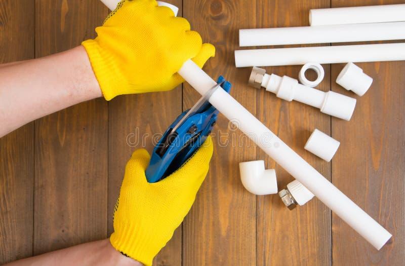 На темной деревянной предпосылке, руки работника в желтых перчатках, scissor белая труба водопровода, конец-вверх стоковое изображение