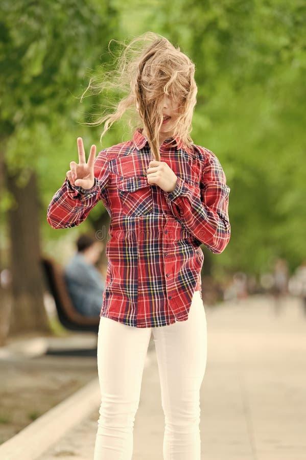 На улице ветрено. Маленький ребенок с грязными волосами в летний день Милый ребенок наслаждается своими волосами и демонстрирует  стоковая фотография rf