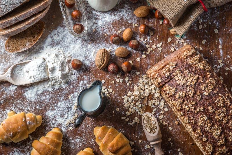 На хлебопекарне, натюрморте с мини круассанами, хлебе, молоке, гайках и муке стоковое изображение rf