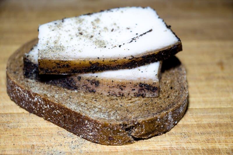 На части черного хлеба, 2 части сала Молодое сало ` s свиньи взбрызнуто с специями черного перца стоковые изображения rf