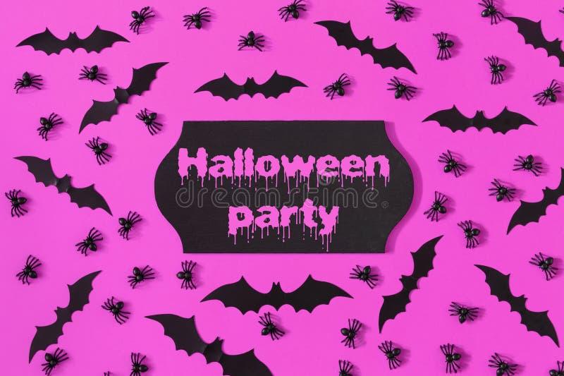 На ярко фиолетовой предпосылке, кладут декоративные пауки и летучие мыши хеллоуина вне В центре черная металлическая пластинка стоковое фото rf
