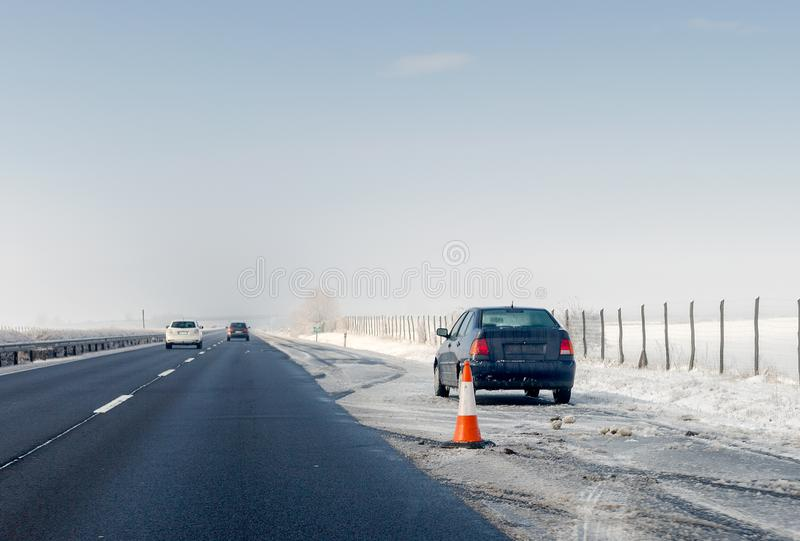 Небезупречный конус автомобиля и движения на аварийной останавливая майне на обочине Проблема с кораблем на шоссе зимы стоковые фото