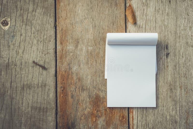 Небольшая белая тетрадь на старой текстуре древесины grunge стоковое фото