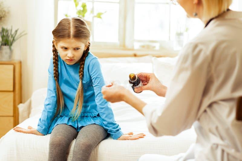 Небольшая больная девушка dissatisfiedly смотря сироп горла педиатра лить стоковая фотография rf