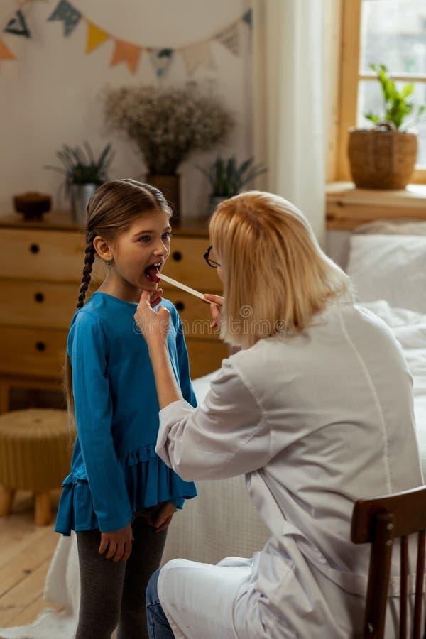 Небольшая больная милая длинн-с волосами маленькая девочка видя otolaryngo стоковое изображение rf