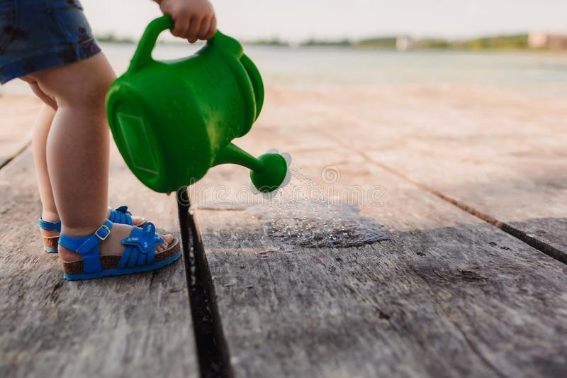 Небольшая девушка играет с моча консервной банкой деревянного моста Весна и лето Садоводство смогите позеленеть мочить стоковые фото