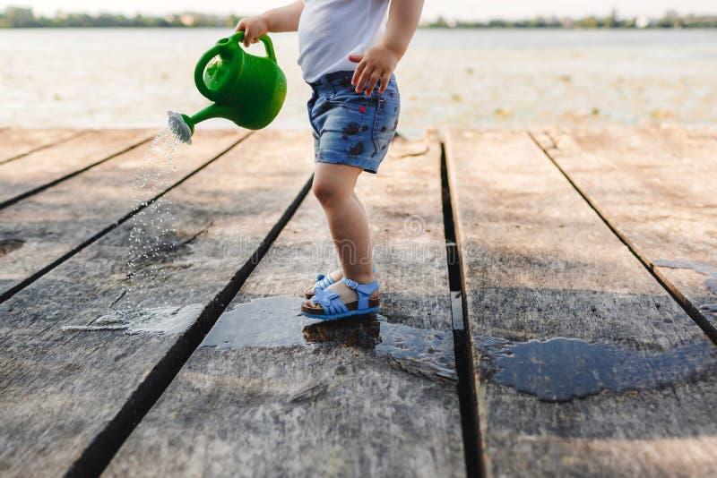 Небольшая девушка играет с моча консервной банкой деревянного моста Весна и лето Садоводство смогите позеленеть мочить стоковые фотографии rf