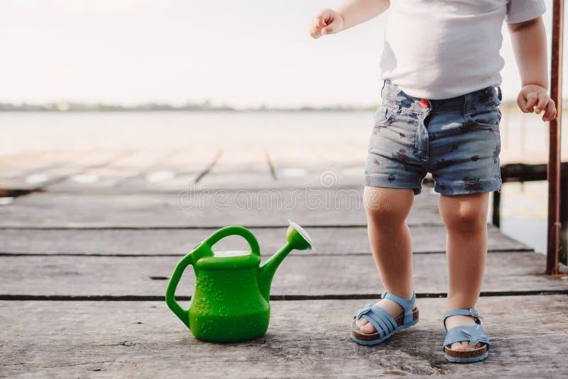 Небольшая девушка играет с моча консервной банкой деревянного моста Весна и лето Садоводство смогите позеленеть мочить стоковое фото