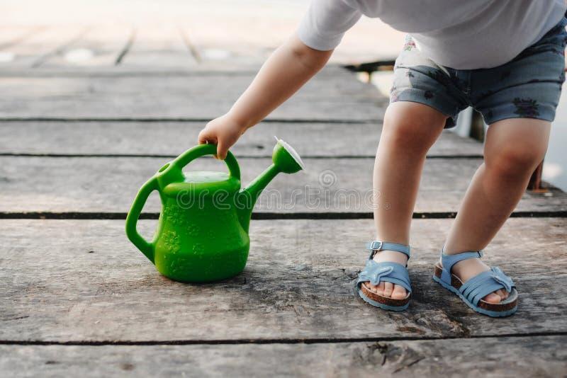 Небольшая девушка играет с моча консервной банкой деревянного моста Весна и лето Садоводство смогите позеленеть мочить стоковые изображения rf