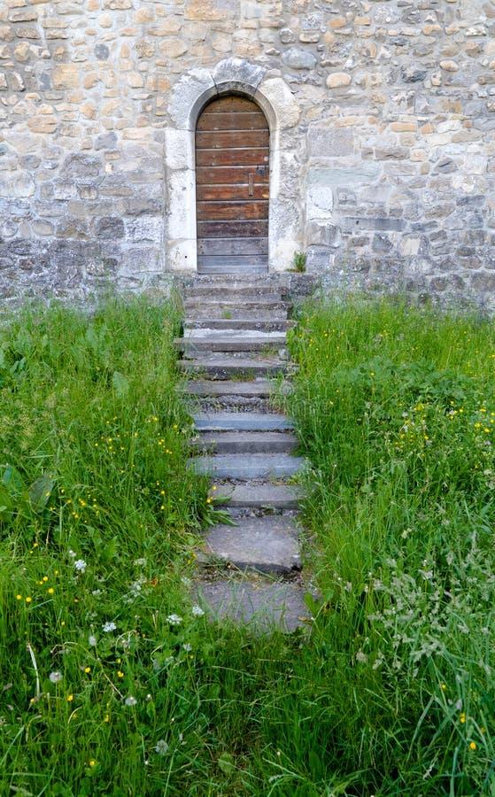 Небольшая деревянная дверь в толстой и массивной средневековой городской стене с шагами водя через траву стоковое изображение rf