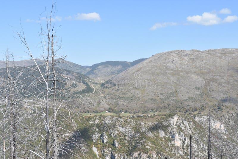 Небольшая изолированная, уединенная деревня установила над наклонами каньона Тара стоковые изображения
