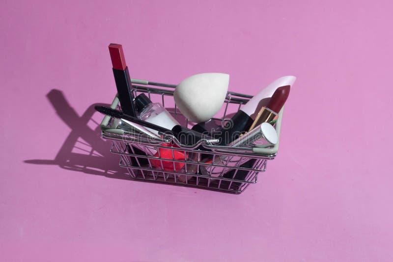 Небольшая корзина от супермаркета с продуктами макияжа стоковое изображение