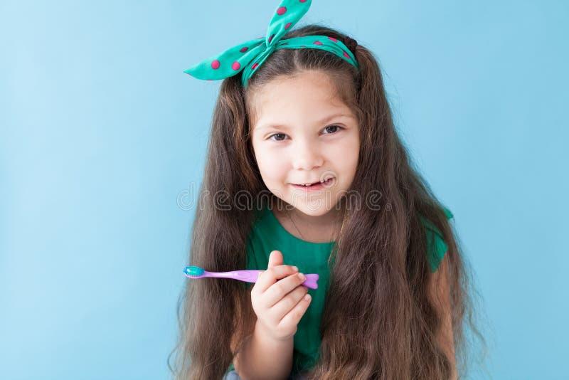 Небольшая красивая девушка очищает зубоврачевание зубной щетки зубов стоковые изображения