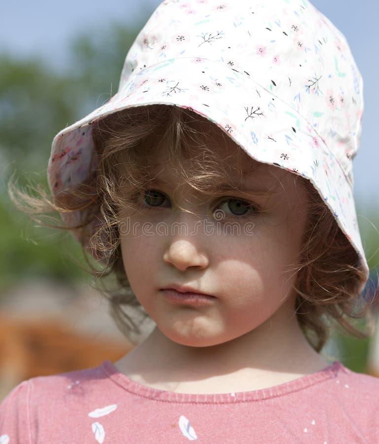Небольшая красивая курчавая девушка выглядит грустной и обиденной Панама, скручиваемости, outdoors стоковые фотографии rf