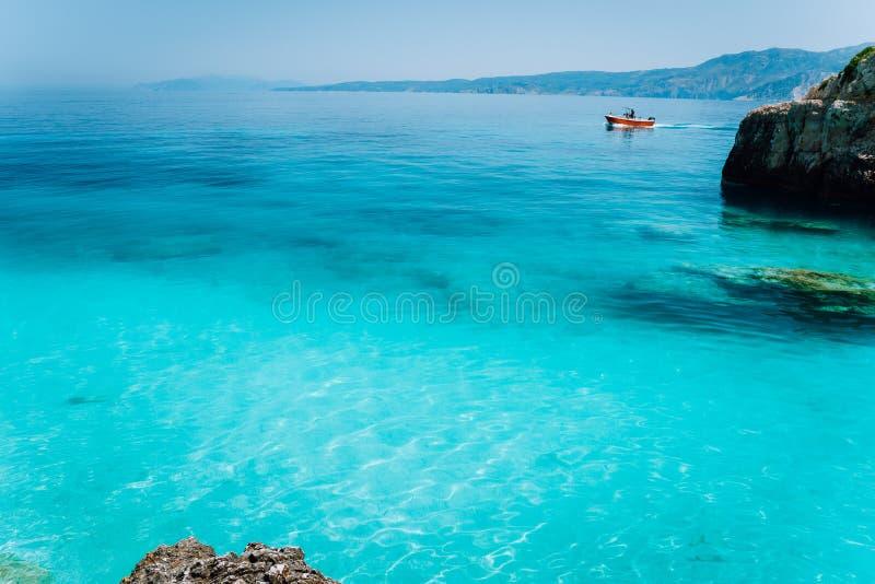 Небольшая красная шлюпка плавая на ясную голубую морскую воду Концепция релаксации каникул пляжа лета стоковые изображения rf