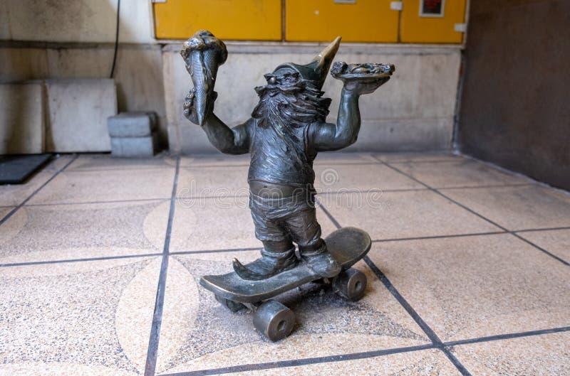 Небольшая скульптура бронзового катания гнома на скейтборде с мороженым стоковое фото rf