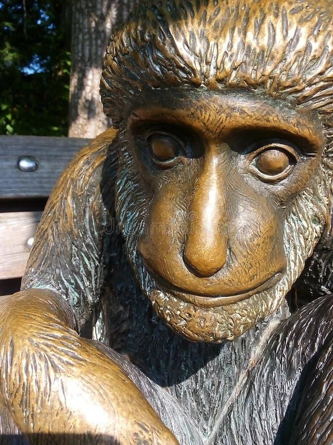 Небольшая скульптура обезьяны сидя на солнечной скамейке в парке стоковая фотография rf