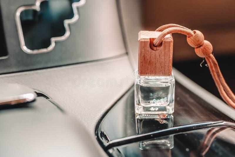 Небольшая стеклянная бутылка с духами автомобиля на черной приборной панели автомобиля стоковое фото rf