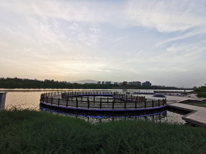Небольшая трава, круглая деревянная загородка, вода озера формирует красивое изображение, очень красивое стоковая фотография