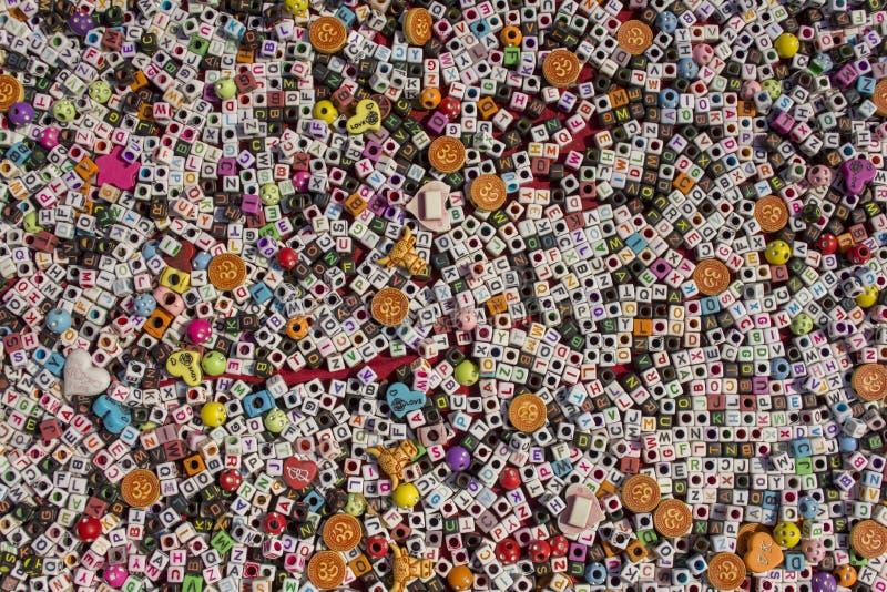 Небольшие белые и черные кубы с отверстиями и ложью английского алфавита на красной поверхности таблицы, пестротканых писем грубы стоковые фото
