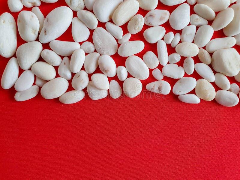 Небольшие белые камни на яркой ткани коралла Текстура, предпосылка, картина, обои ок стоковые фото