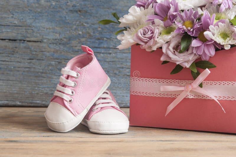 Небольшие ботинки ребенка и красивый букет цветка на деревянной плате стоковые изображения rf
