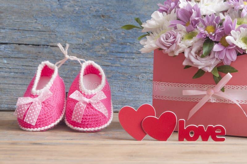 Небольшие ботинки ребенка и красивый букет цветка на деревянной плате стоковая фотография rf