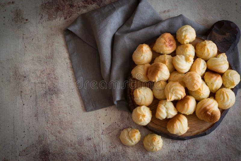 Небольшие вкусные profiteroles на деревянной доске стоковое изображение