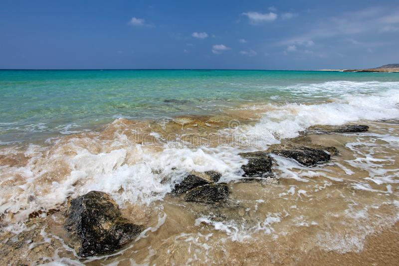 Небольшие волны моря задавливая на черных утесах на песчаном пляже, beautifu стоковые фотографии rf