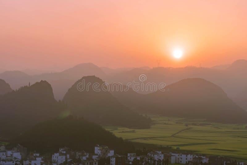 Небольшие деревни с цветками рапса на пике цыпленка JinjifengGolden, Китае стоковые изображения rf
