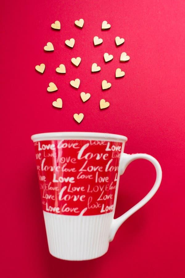 Небольшие деревянные сердца летают из красной чашки с любовью надписи стоковое изображение