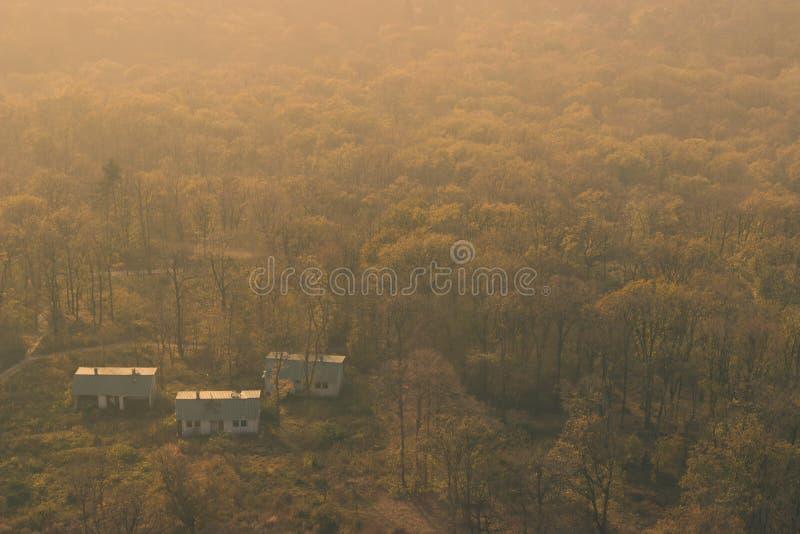 Небольшие дома в древесинах, на холодный день осени стоковое фото rf