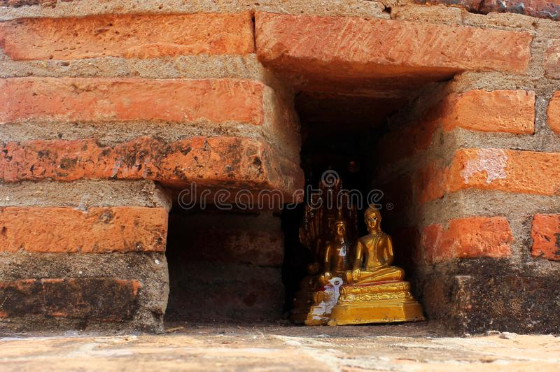 Небольшие золотые статуи Будды спрятанные в красной кирпичной стене стоковая фотография