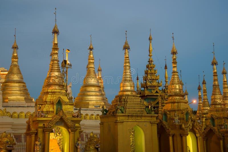 Небольшие золотые stupas пагоды в выравниваясь сумерках, Янгона Shwedagon стоковые изображения rf