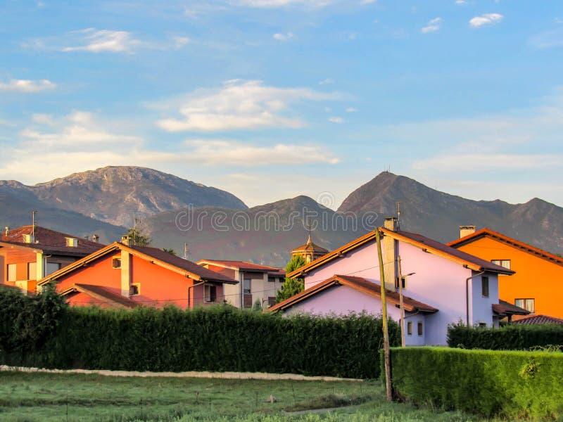 Небольшие красочные дома окруженные зеленой естественной загородкой с Cantabrian горами на предпосылке стоковое фото rf