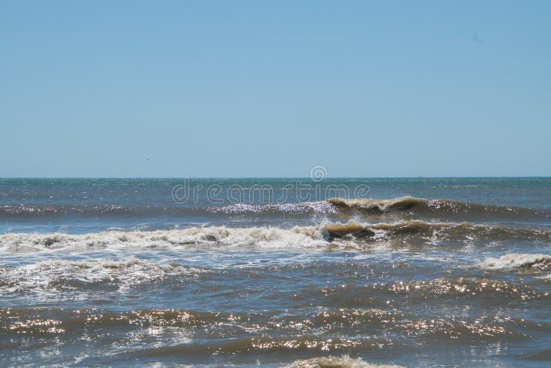 Небольшие ломая волны на пляже с темной коричневой водой океана стоковое изображение