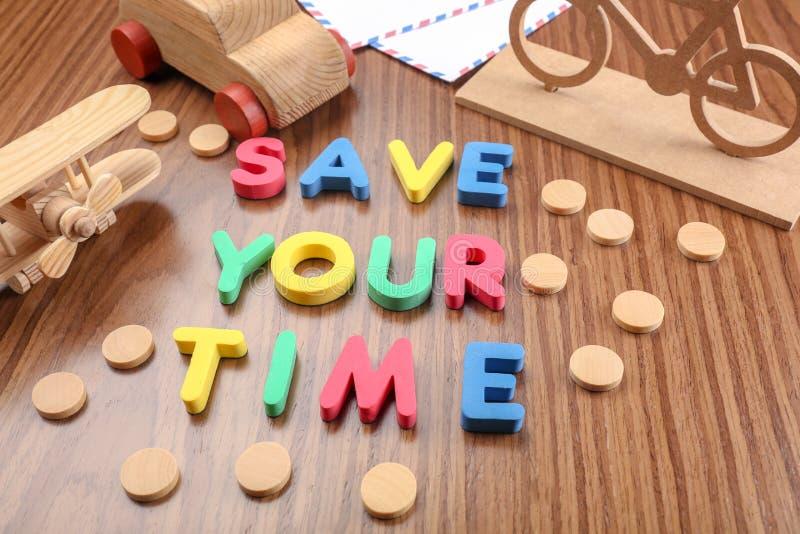 Небольшие переход и фраза \ «спасение игрушки ваше время \» составленный от писем на деревянном столе стоковая фотография
