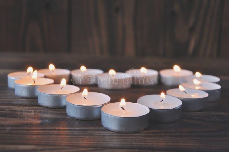 Небольшие свечи - таблетки стоят на деревянном столе стоковая фотография rf