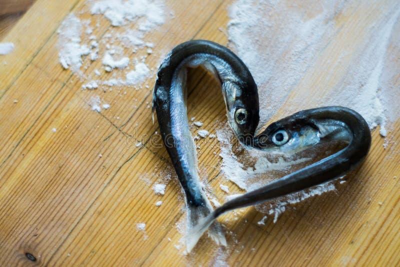 Небольшие серебряные рыбы моря положенные вне в форме сердца стоковое фото