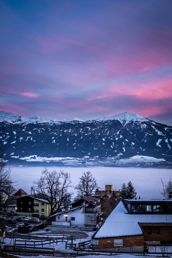 Небольшие снежные дома в городке с изумляя небом и горами стоковое изображение rf
